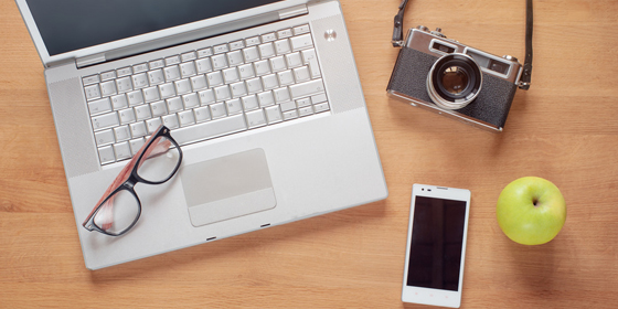 Overhead of modern comfort work place. Different objects on wooden background. Items include camera, glasses, laptop, smartphone and apple