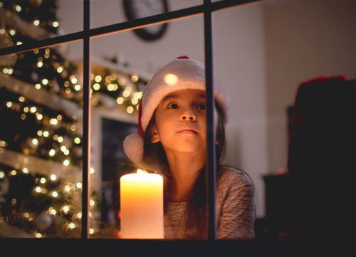 girl looking out the window on Christmas